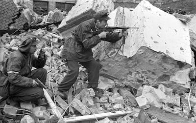 Two armed Polish soldiers fighting through the rubble of Warsaw.